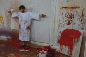 Ateliermitarbeiter in Kreuzigungspose und Malerkutte