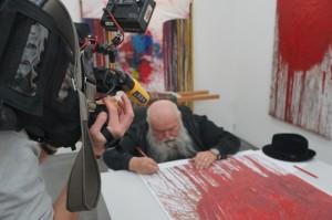 Hermann Nitsch signiert die neue Grafik Schüttbild I live für RTL West